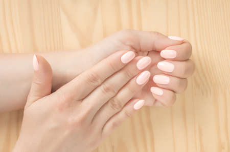 Closeup shot of a woman in a nail salon getting a manicur. wooden background. Beautiful groomed woman's hands with white pink nails. perfect, groomed woman's hands Nails care. Manicure beauty salon. Archivio Fotografico