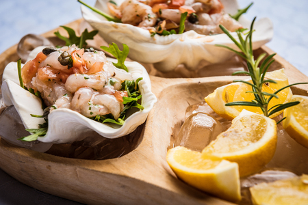 Wooden dish with sea food, lemon and ice.