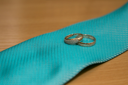 Wedding rings on green tie