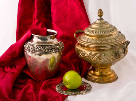 antique dishes: antique dishes and apple draped by red fabrics