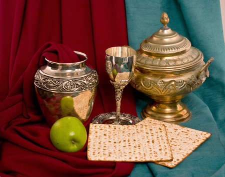 seyder: antique dishes and apple and matzo draped by colour fabrics