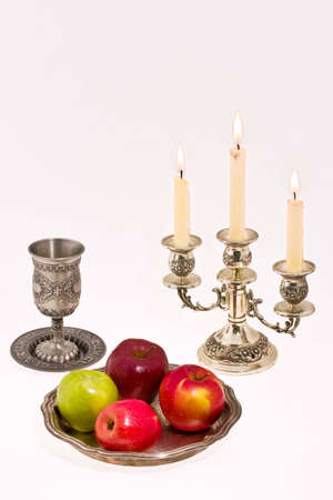 kiddush: cup candlestick and apple dish on white background