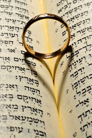 Wedding ring gives the shadow of the heart in the Bible open at the Solomon's Song of Solomon Stock Photo - 4715219
