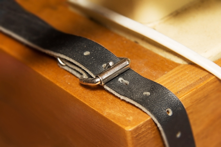 strap on: old Genuine leather strap on wood background