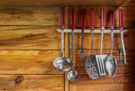 cooking implement: kitchen utensils on the wall on a wooden background Stock Photo