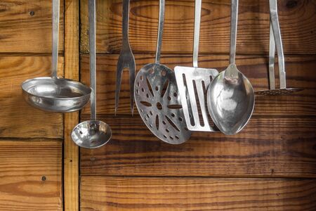kitchen tool: kitchen utensils on the wall on a wooden background Stock Photo