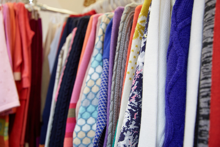 children's wear: Childrens clothing of different colors hanging on hangers in the childrens store Stock Photo