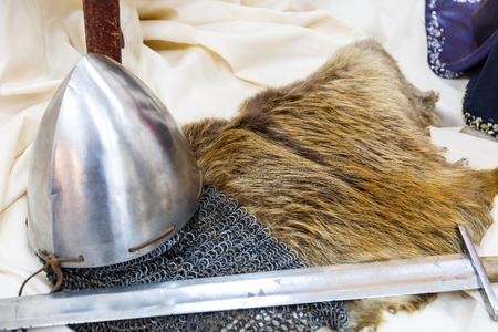 Sword helmet and chain mail lie on wool skin