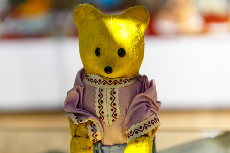 Beautiful teddy bears from around the world stand on the shelf in a toy store