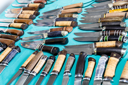 Hunting knives and knifes of large and small sizes lie on a table in a hunting and fishing store Stock Photo