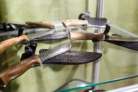 Hunting knives in harnesses lie on a shelf in a hunting shop Stock Photo