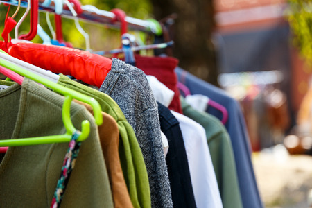 vintage furniture: Hangers with mens and womens clothing at the garage sale