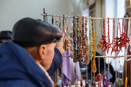 a woman chooses a ring, a necklace with precious stones in a jewelry store Stock Photo
