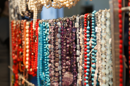 Beads, baubles and bracelets with precious stones and pearls hang in a jewelry store shop Stockfoto