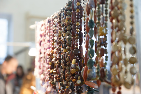 Beads, baubles and bracelets with precious stones and pearls hang in a jewelry store shop Stock Photo