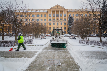 Tractor cleaning the road from the snow. Excavator cleans the streets of large amounts of snow in city. Workers sweep snow from road in winter, Cleaning road from snow storm.