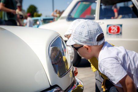 MINSK, BELARUS - MAY 1, 2017: interested child sees a light headlight old classic car Editorial