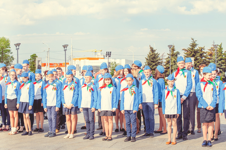 MINSK, BELARUS - MAY 1, 2017: Pupils-pioneers with pioneer neckties do salute on event for initiation for pioneers. Red flags in their hands.