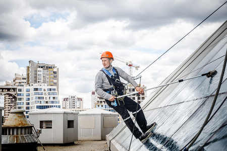 MINSK, BELARUS - 02 JUNE. 2018: group of workers cleaning windows service on high rise building. work on the heights , industrial mountaineering