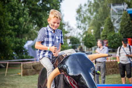 MINSK, BELARUS - MAY 1, 2017: A child enjoys the adrenaline rush while securely strapped a mechanical bull amusement ride