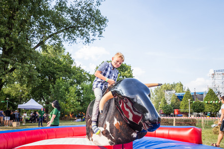 MINSK, BELARUS - MAY 1, 2017: A child enjoys the adrenaline rush while securely strapped a mechanical bull amusement ride Editorial
