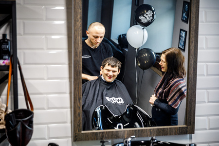 MINSK, BELARUS - 1 APRIL, 2019: a guy with down syndrome get a haircut in barbershop