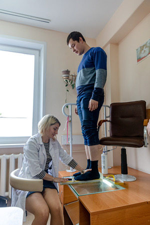 MINSK, BELARUS - 1 JUNE, 2019: man consulting foot doctor in his clinic Éditoriale