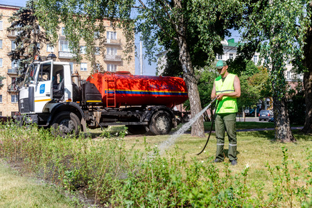 MINSK, BELARUS - 1 JUNE, 2019: utility worker gardener of municipality with hose for watering the plants and trees in city park 報道画像