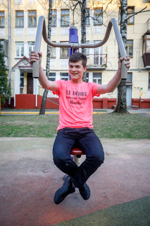 MINSK, BELARUS - 1 MAY, 2019: children, adults and old people exercise on outdoor exercise machines Editorial