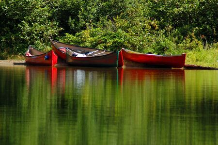 Colourful canoes around the portage Imagens