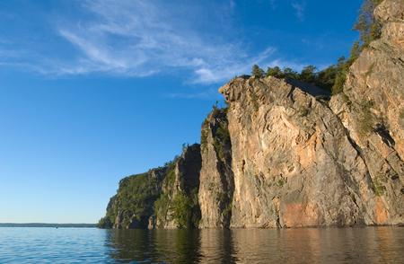석양 빛에 Mazinaw 호수의 해안에서 높은 절벽