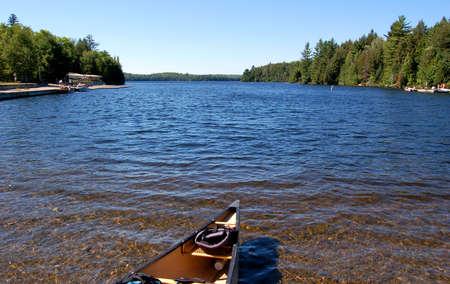 Algonquin Park의 햇살 가득한 소나무 숲에서 운반 후 호수와 카누 스톡 콘텐츠