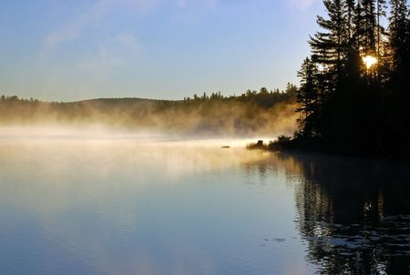 Sunrise and mist in beautiful lake in Algonquin Park