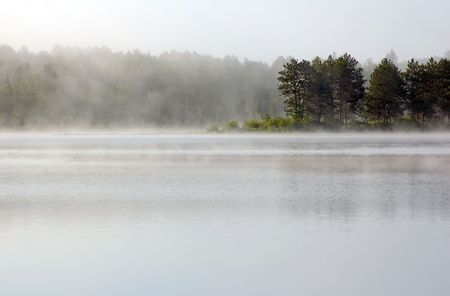 Fog above lake in the morning.