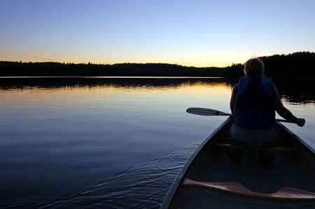 Algonquin Park의 조용한 호수에서의 일몰과 카누 여행 스톡 콘텐츠