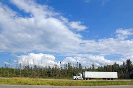 transporte de mercancia: Cami�n de carga en la autopista de Canad� bajo nube azul cielo Foto de archivo