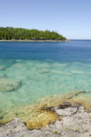 huron: Green and blue water of Huron Lake, Ontario under blue sky.