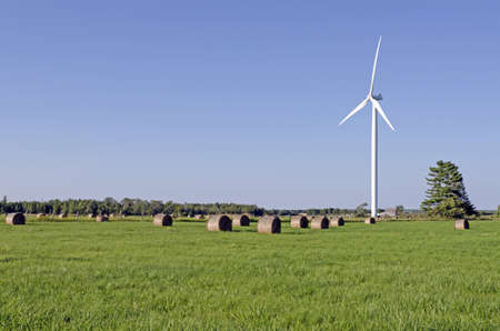 Wind turbine and hay bails in a field on green grass background photo
