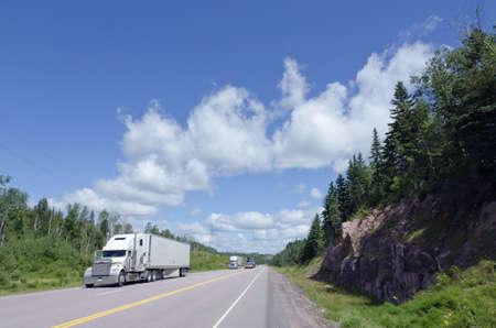 구름이 파란 하늘 아래 트랜스 캐나다 고속도로에화물 트럭