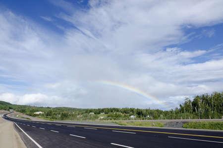 spaciousness: TransCanada highway along Superior Lake shore under rainbow