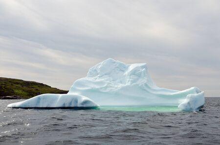 Bright white iceberg on dark water and rock background