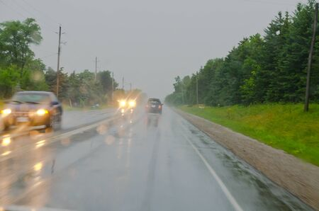 Countryside road and several cars in rainy overcast day. Canada Stock Photo