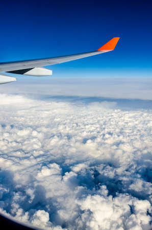 Plane wing, white clouds and blue sky
