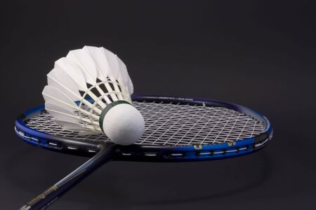 racket and shuttlecock over black