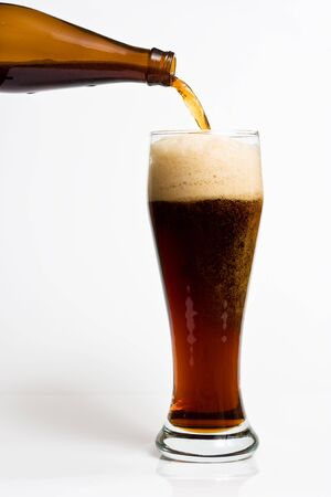 A beer pouring into a glass on the white background Stock Photo - 6453386