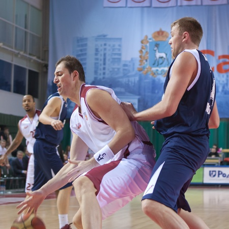 pbl: SAMARA, RUSSIA - JANUARY 22: Primoz Brezec of BC Krasnye Krylia with ball attacking player of BC Triumph January 22, 2011 in Samara, Russia. Editorial