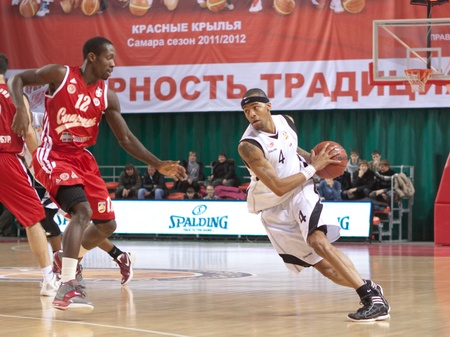 pbl: SAMARA, RUSSIA - NOVEMBER 25: Brion Rush of BC Krasnye Krylia with ball tries to go past a BC Spartak player on November 25, 2011 in Samara, Russia. Editorial