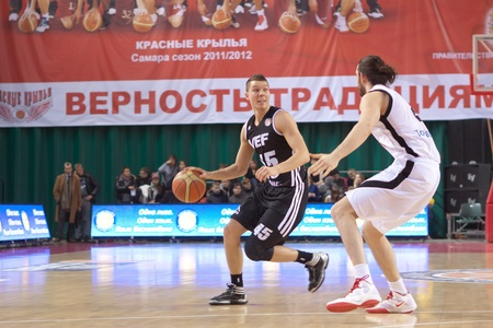 bc vef riga: SAMARA, RUSSIA - DECEMBER 23: Dairis Bertans of BC VEF with ball goes against a BC Krasnye Krylia player on December 23, 2011 in Samara, Russia.