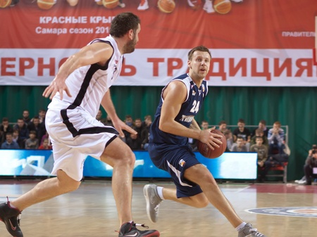 pbl: SAMARA, RUSSIA - JANUARY 28: Victor Zvarykin of BC Triumph with ball tries to go past a BC Krasnye Krylia player on January 28, 2012 in Samara, Russia.