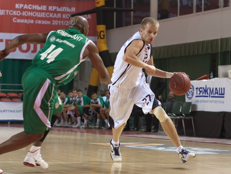 pbl: SAMARA, RUSSIA - APRIL 17: Alexey Surovtsev of BC Krasnye Krylia with ball tries to go past a BC UNICS player on April 17, 2012 in Samara, Russia.